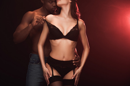 Cropped view of African American man undressing woman in lingerie on dark with red light and copy space