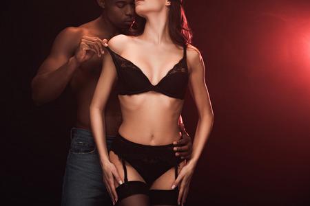 Vista recortada del hombre afroamericano que desnuda a la mujer en ropa interior en la oscuridad con luz roja y espacio de copia
