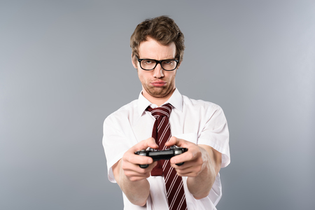 Upset businessman playing video game with joystick on grey background
