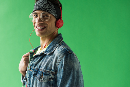 handsome mixed race man in headphones looking at camera and smiling while listening music on green screen