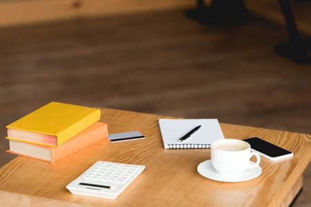 wooden table with books, calculator, credit card, coffee cup, notebook and smartphone with blank screen
