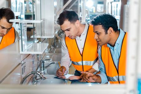 selective focus of attentive multicultural colleagues working in plumbing department Foto de archivo - 121417712