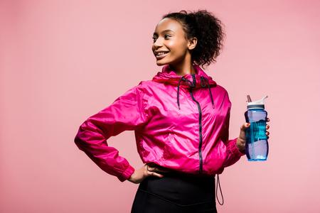 bella sorridente sportiva afroamericana con bottiglia sportiva isolata su pink Archivio Fotografico