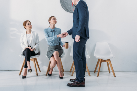 cropped view of recruiter shaking hands with employee sitting on chair with paper cup