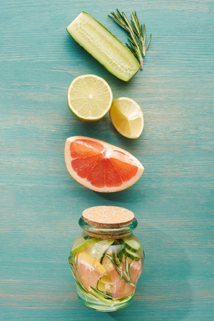 top view of detox drink in jar with lemons, limes, grapefruits, cucumbers and rosemary