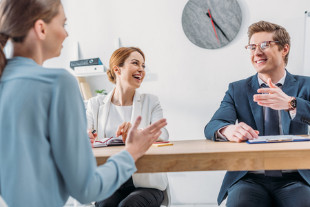 cheerful recruiter looking at coworker in glasses gesturing while speaking with attractive applicant Imagens