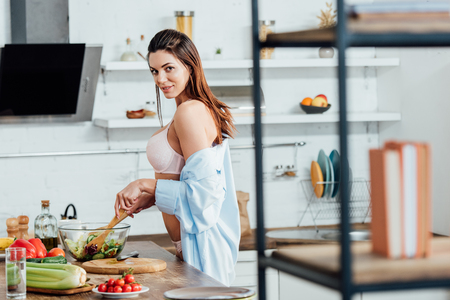 Sexy girl in underwear and shirt cooking vegetable salad
