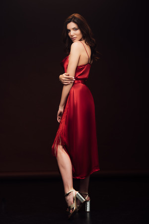 Beautiful sensual woman in red dress posing and looking at camera isolated on black background