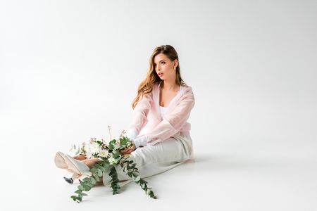 pretty young woman sitting with flowers and green eucalyptus on white 스톡 콘텐츠