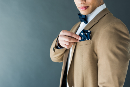 cropped view of stylish mixed race man in suit adjusting napkin isolated on grey with copy space Stockfoto