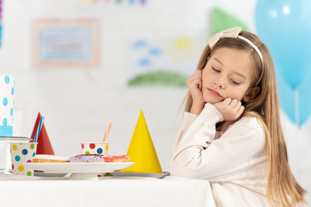 upset kid sitting at table with donuts and party caps during birthday celebration