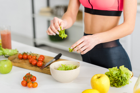 cropped view of sportswoman holding salad leaves near bowl