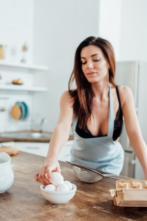 Sexy woman in underwear and blue apron holding eggs in kitchen