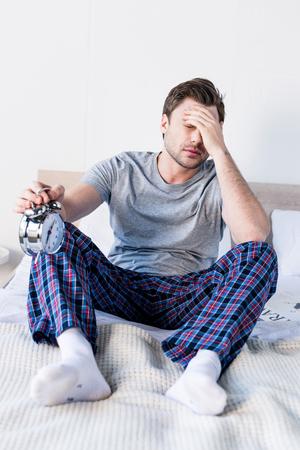 Schöner verschlafener Mann, der zu Hause auf dem Bett sitzt und Wecker hält Standard-Bild