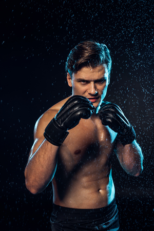 Front view of boxer in leather gloves standing under water drops on black