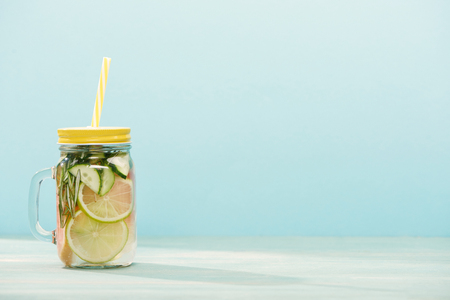 detox drink in jar with lime, cucumber and straw isolated on blue