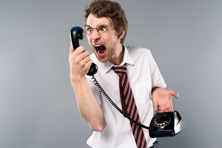 angry businessman in glasses screaming in vintage phone Stock Photo