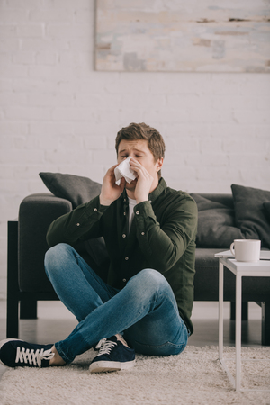 man sitting on carpet with crossed legs and sneezing in tissue near coffee table with cup of coffee