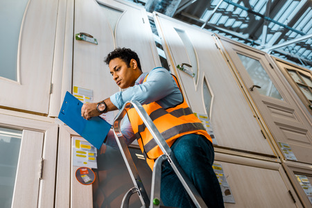 handsome serious indian worker in safety vest standing on ladder near doors