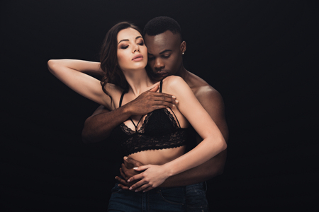 african american man passionately hugging woman in lace bra isolated on black