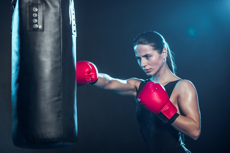 Boxeador cansado en guantes de boxeo rojos entrenando con saco de boxeo en negro