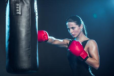 Pugile stanco in guanti da boxe rossi che si allenano con il sacco da boxe sul nero