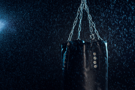 Leather punching bag hanging on steel chains under water drops on black Stock fotó