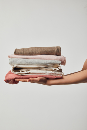 Cropped view of woman holding folded ironed clothes isolated on grey