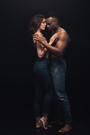 beautiful interracial couple in denim embracing isolated on black