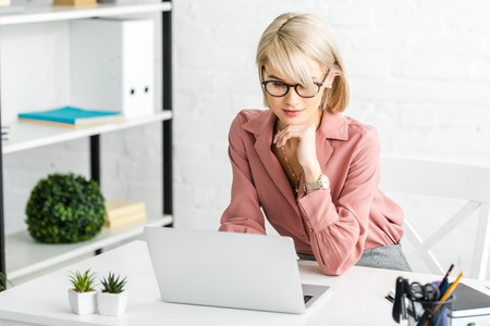 pensive young blonde freelancer in glasses looking at laptop