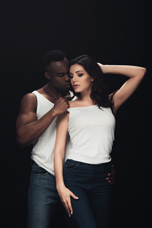 handsome african american man undressing beautiful sensual woman isolated on black Imagens