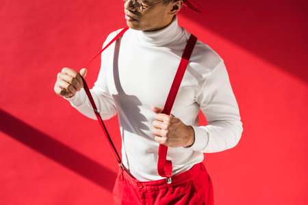 cropped view of fashionable mixed race man in suspenders posing on red