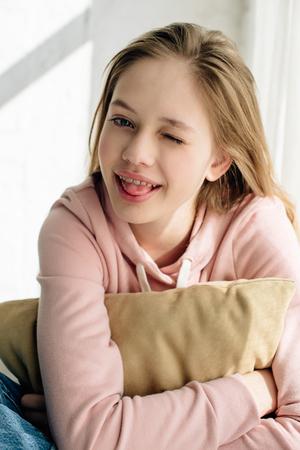 Adolescente sorridente che abbraccia il cuscino marrone e guarda la telecamera Archivio Fotografico