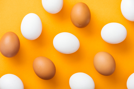 top view of whole white and brown fresh chicken eggs on bright orange background Stock Photo