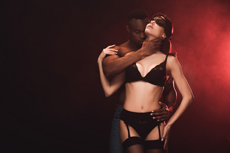 african american man embracing beautiful sexy woman in lace mask on black with copy space 版權商用圖片