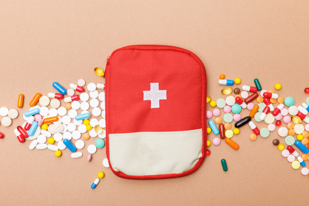 Top view of first aid kit bag and colorful pills on brown surface Foto de archivo - 121418605
