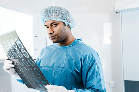 good-looking doctor in medical cap and uniform holding x-ray and looking at camera