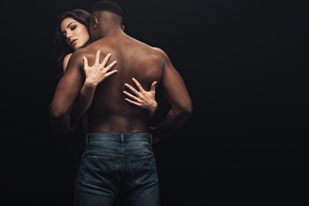 back view of beautiful woman hugging shirtless african american man isolated on black