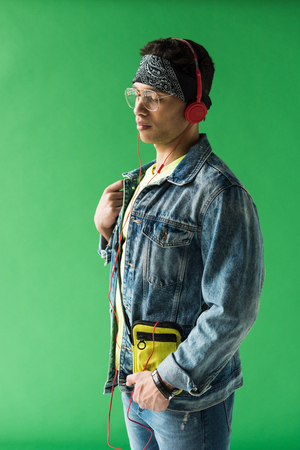 handsome mixed race man in headphones and denim listening music on green screen