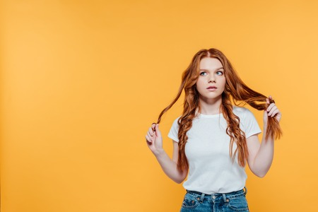 beautiful redhead girl touching hair and looking away isolated on yellow with copy space