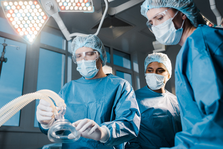 doctors and nurse in uniforms and medical caps holding mask in operating room