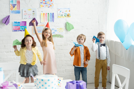 adorable smiling kids playing with paper planes during birthday party at home