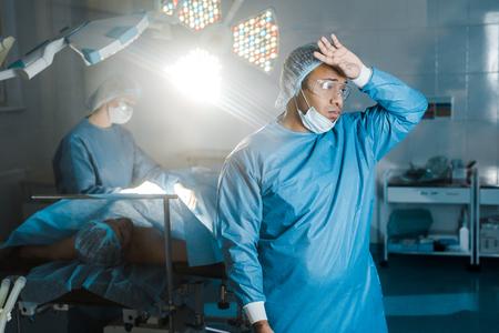 Arzt in Uniform und medizinischer Maske, der im Operationssaal wegschaut