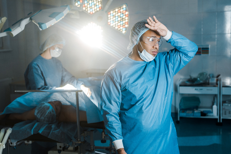 doctor in uniform and medical mask looking away in operating room