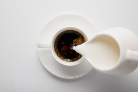 Draufsicht auf Tasse Kaffee und Kanne Milch auf Weiß