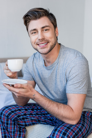 handsome smiling man in pyjamas holding coffee cup and looking at camera