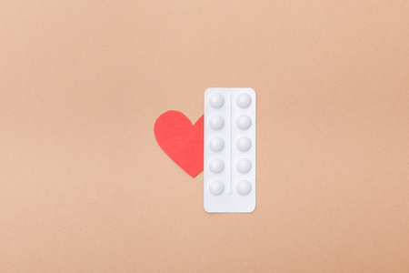Top view of blister with pills and paper heart isolated on brown 版權商用圖片