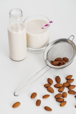 vegan almond milk in bottle and glass with straw near scattered almonds and sieve Stockfoto