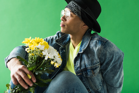 stylish mixed race man in denim posing with flowers on green screen Stock Photo
