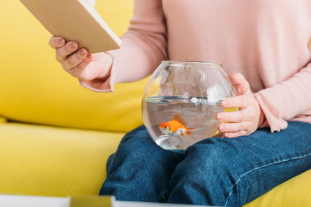 partial view of woman holding book while sitting with fish bowl on knees Imagens